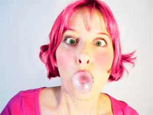girl with pink hair blowing bubble